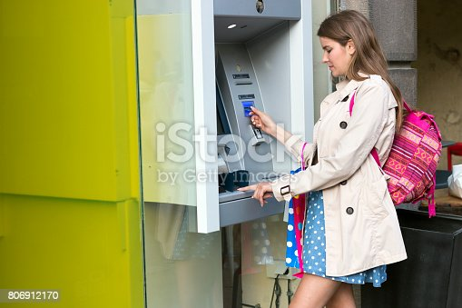 945598452 istock photo Beautiful girl inserting a credit card to ATM machine 806912170