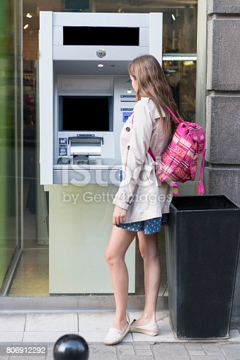 945598452 istock photo Beautiful girl inserting a credit card to ATM machine 806912292