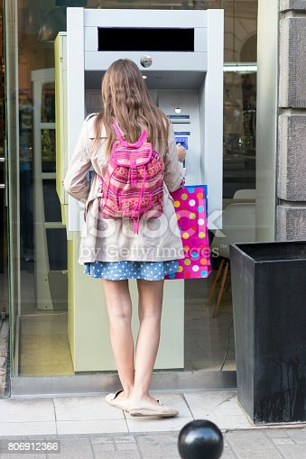 945598452 istock photo Beautiful girl inserting a credit card to ATM machine 806912366