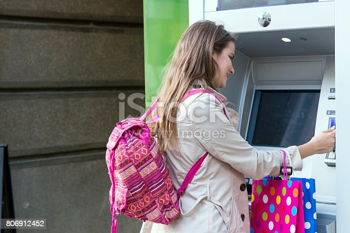 945598452istockphoto Beautiful girl inserting a credit card to ATM machine 806912452
