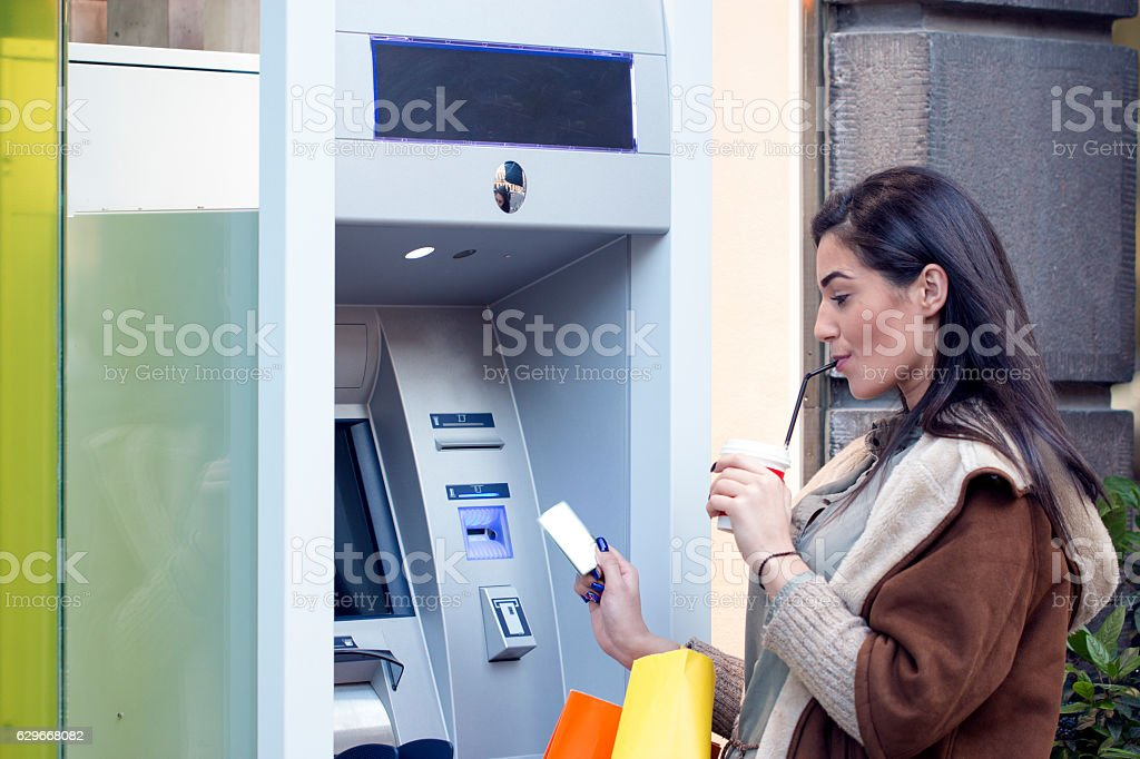 Beautiful girl inserting a credit card to ATM stock photo