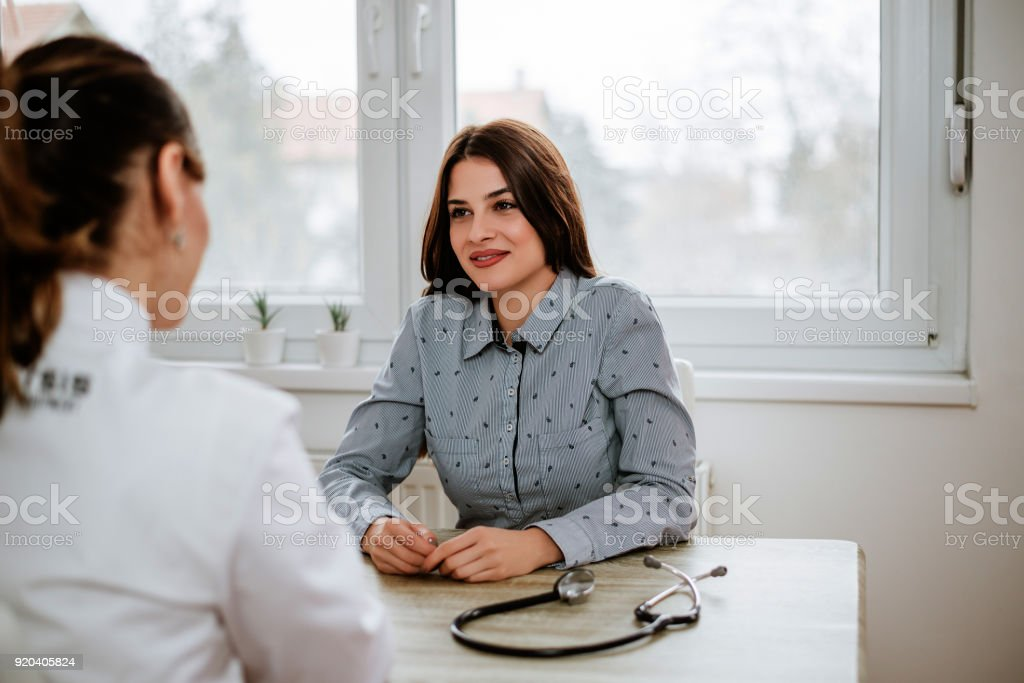 Beautiful girl is consulting with gynecologist stock photo