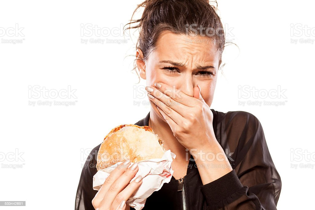 Beautiful girl is disgusted by her sandwich stock photo