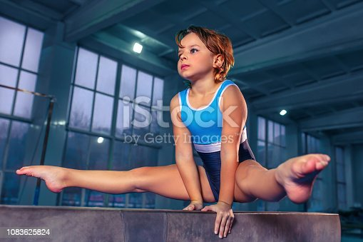 The beautiful little girl is engaged in sports gymnastics on a log at gym. The performance, sport, acrobat, acrobatic, exercise, training concept