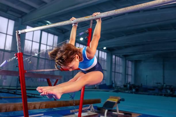 hermosa chica se dedica a la gimnasia deportiva en una barras paralelas - gimnasia fotografías e imágenes de stock