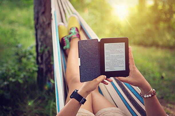 Beautiful girl is reading e-book in the hammock stock photo