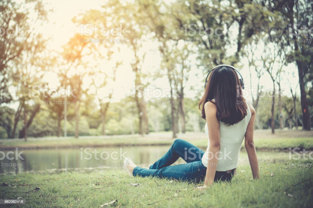 Beautiful Girl Is Relaxing By Listening To Music In The Park