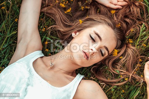 Beautiful girl is relaxing lying on the grass
