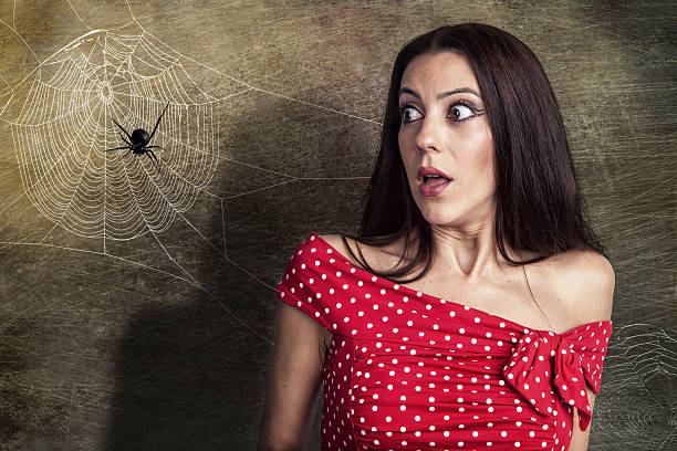 Beautiful girl is scared of a spider stock photo
