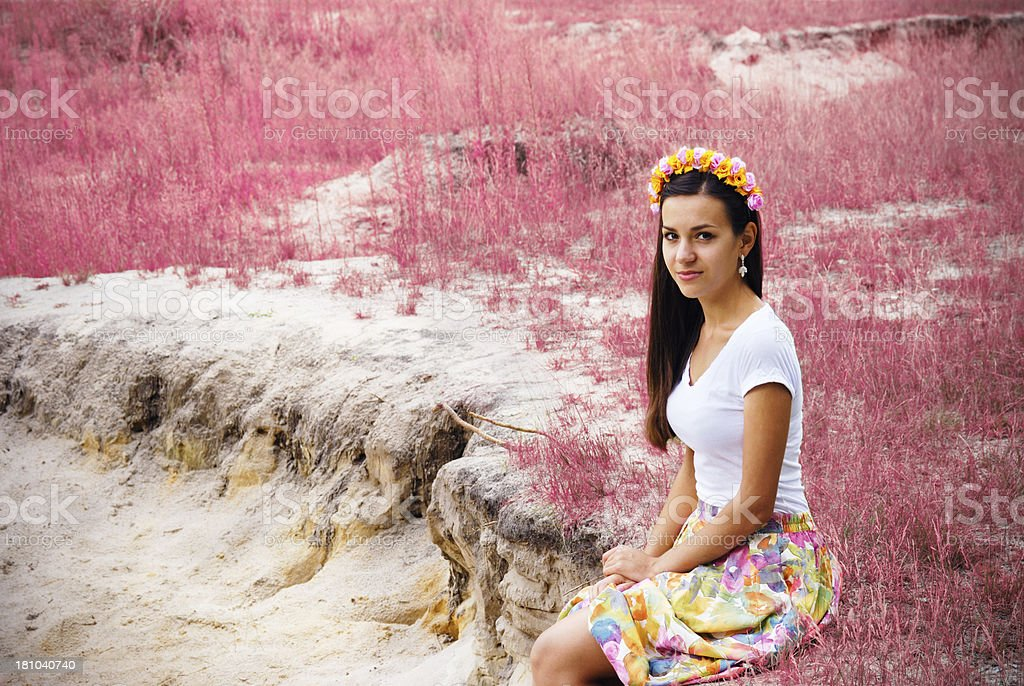 Beautiful girl is sitting near pink flowers field royalty-free stock photo