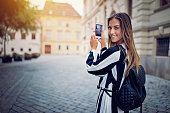 Beautiful girl is taking pictures in small town with her mobile phone