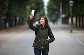 Beautiful girl is taking selfie in the autumn forest