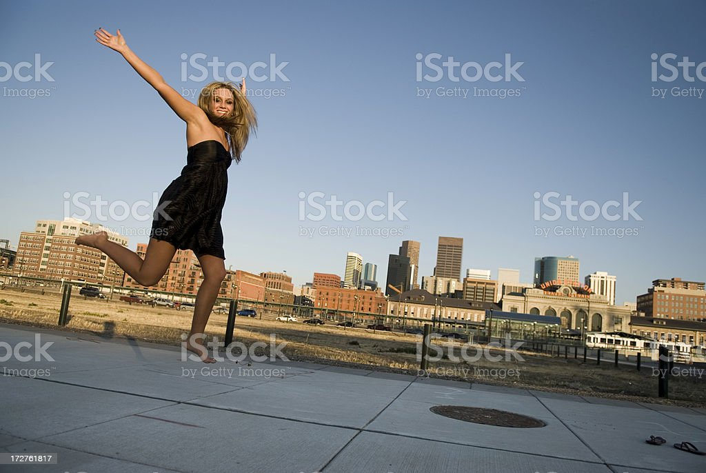 Beautiful Girl Jumps in Front of Skyline stock photo