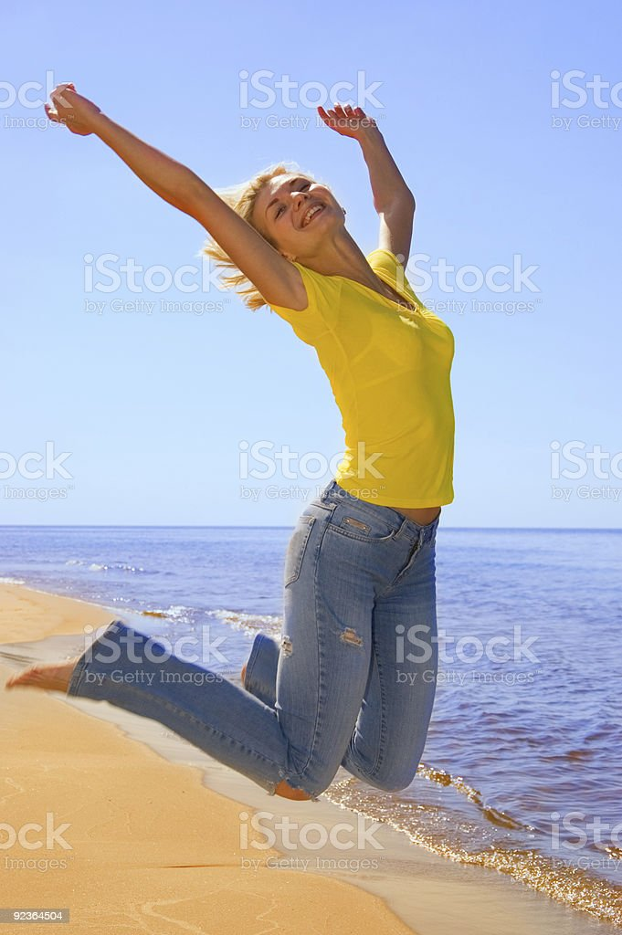 Beautiful girl jumps on a beach royalty-free stock photo