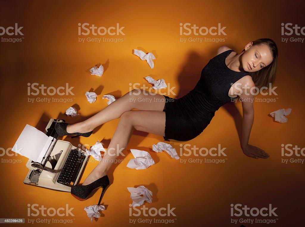 Beautiful girl lies at the typewriter. royalty-free stock photo
