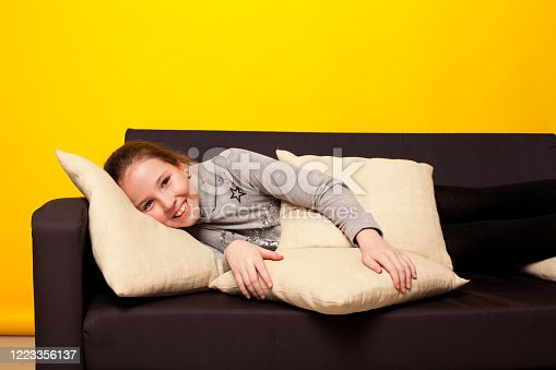 1003539592 istock photo beautiful girl lies on a black sofa in homemade clothes with pillows 1223356137
