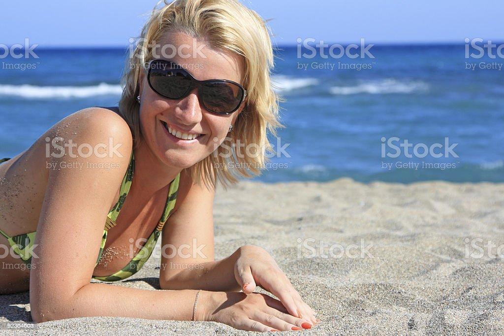 beautiful girl lies on  beach at  sea royalty-free stock photo