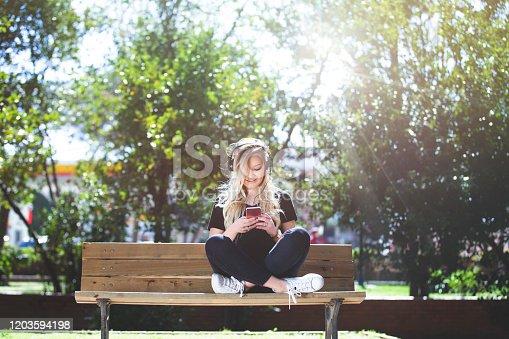Beautiful girl listening music at park