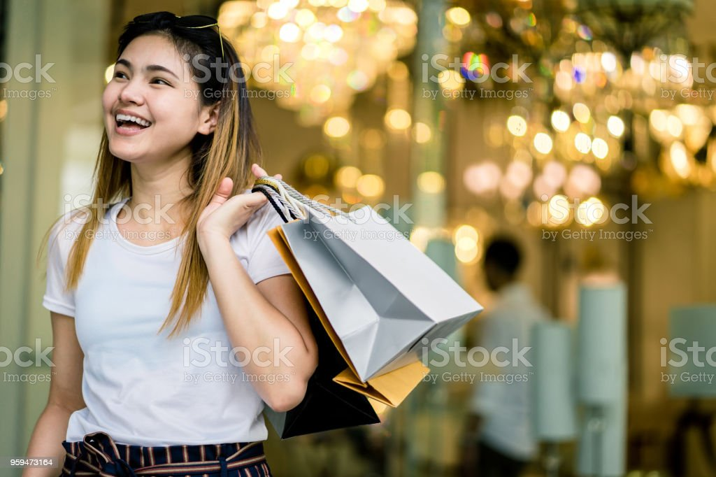 Beautiful girl long hair She is happily shopping at the street mall, She holds several bags of paper, light bokeg copy space the photo. stock photo