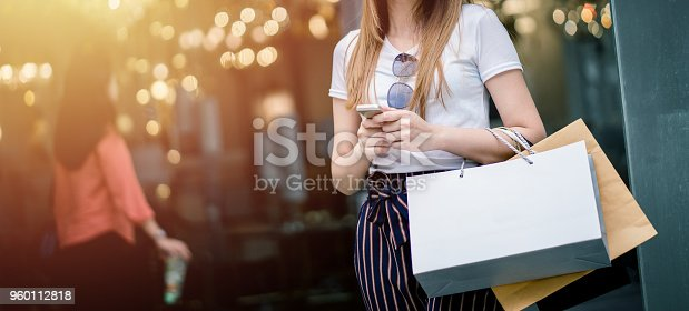 istock Beautiful girl long hair She is happily shopping at the street mall, She holds several bags of paper and mobile phone, Light bokeh copy space the photo. 960112818