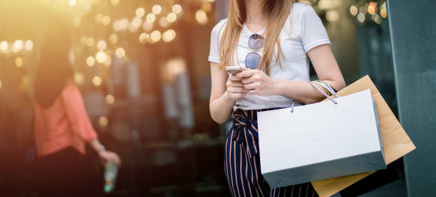 beautiful girl long hair she is happily shopping at the street mall, she holds several bags of paper and mobile phone, light bokeh copy space the photo. - online shopping imagens e fotografias de stock