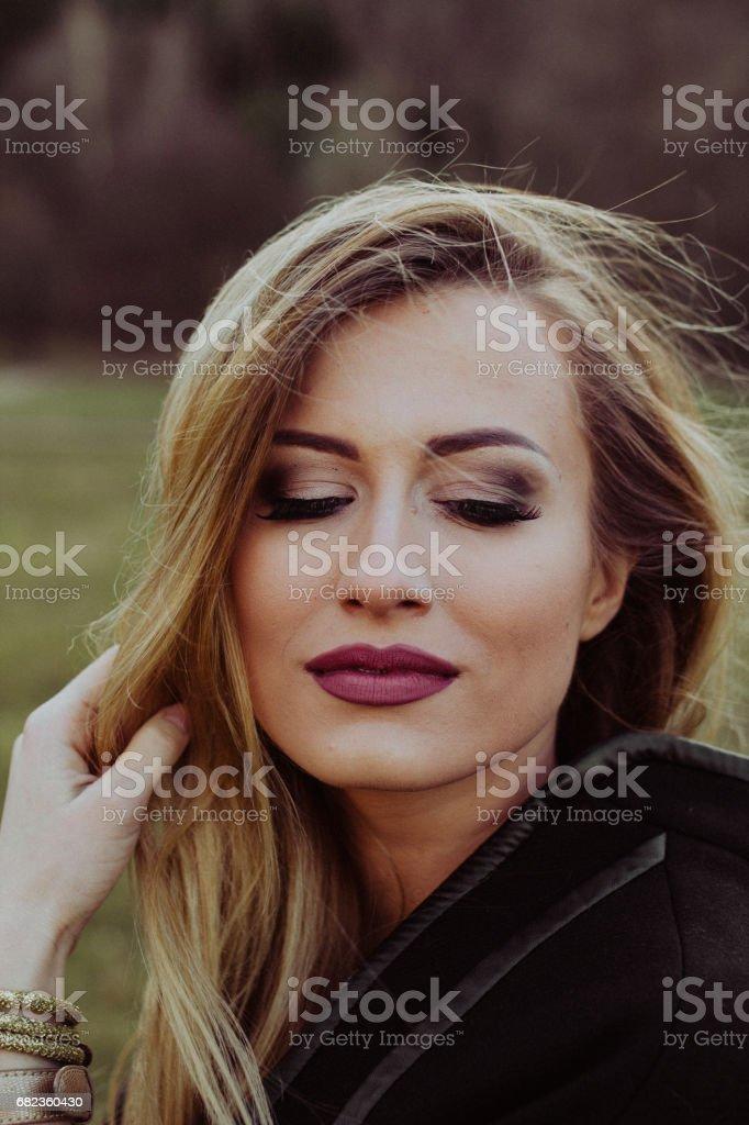 Vacker flicka ser tillbaka med ett litet leende royaltyfri bildbanksbilder