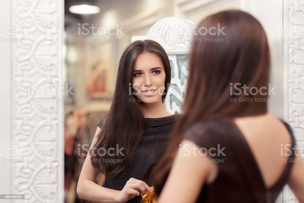 Beautiful Girl Looking in the Mirror and Trying a Dress stock photo