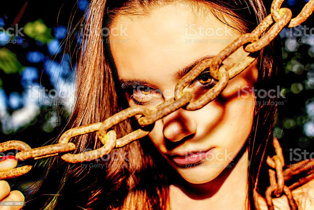 Beautiful  girl looking through the hole of a rasty chain stock photo