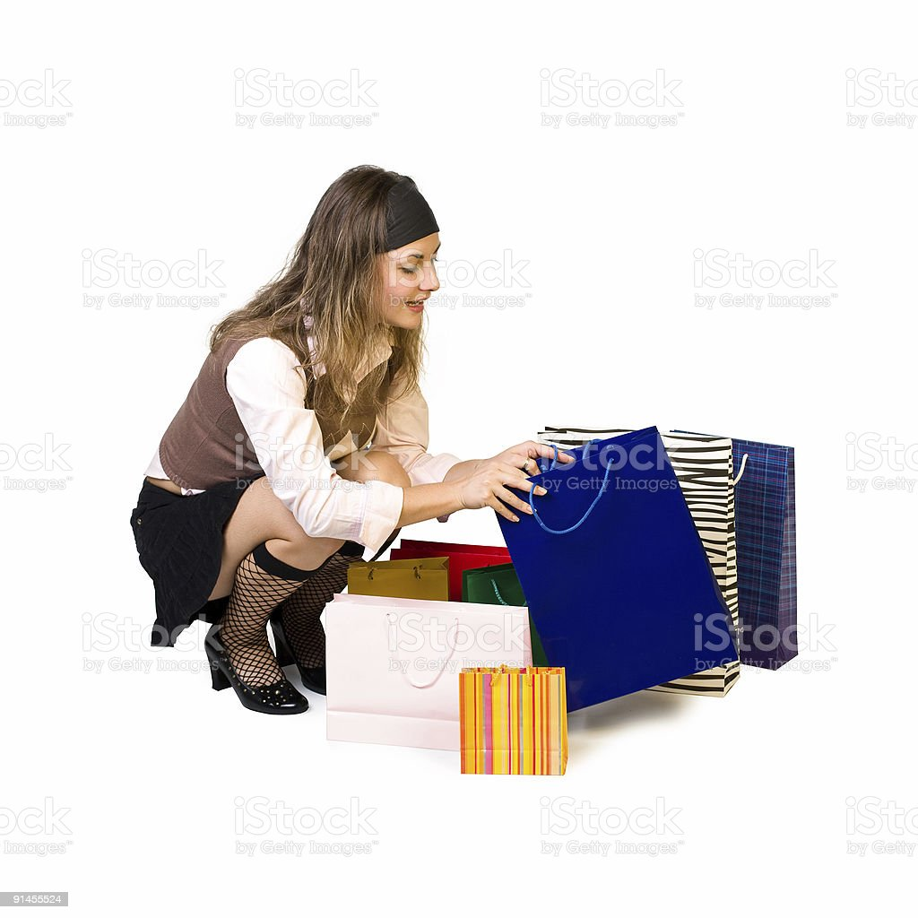 beautiful girl looks in shoppingbag and smiles royalty-free stock photo
