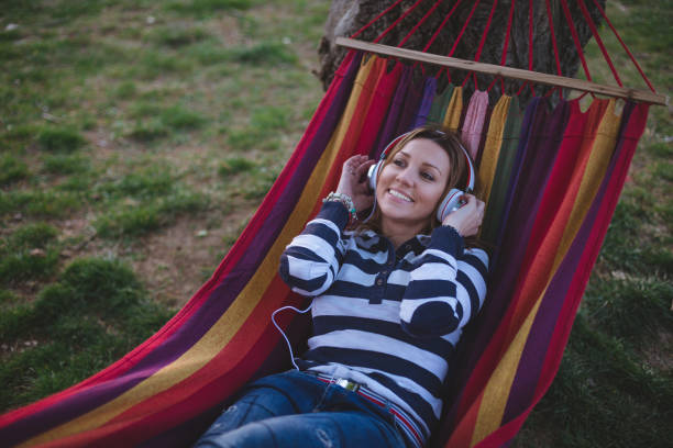 Beautiful girl lying in a hammock in a park and enjoying music stock photo