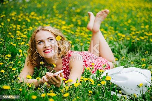 istock Beautiful girl lying on the field with dandelions and headphones. 533326102