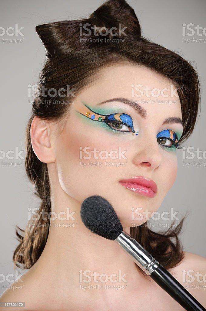Beautiful girl makes a makeup stock photo