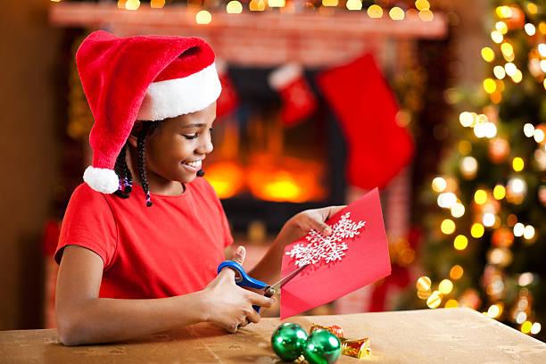 Beautiful girl making Christmas cards. stock photo