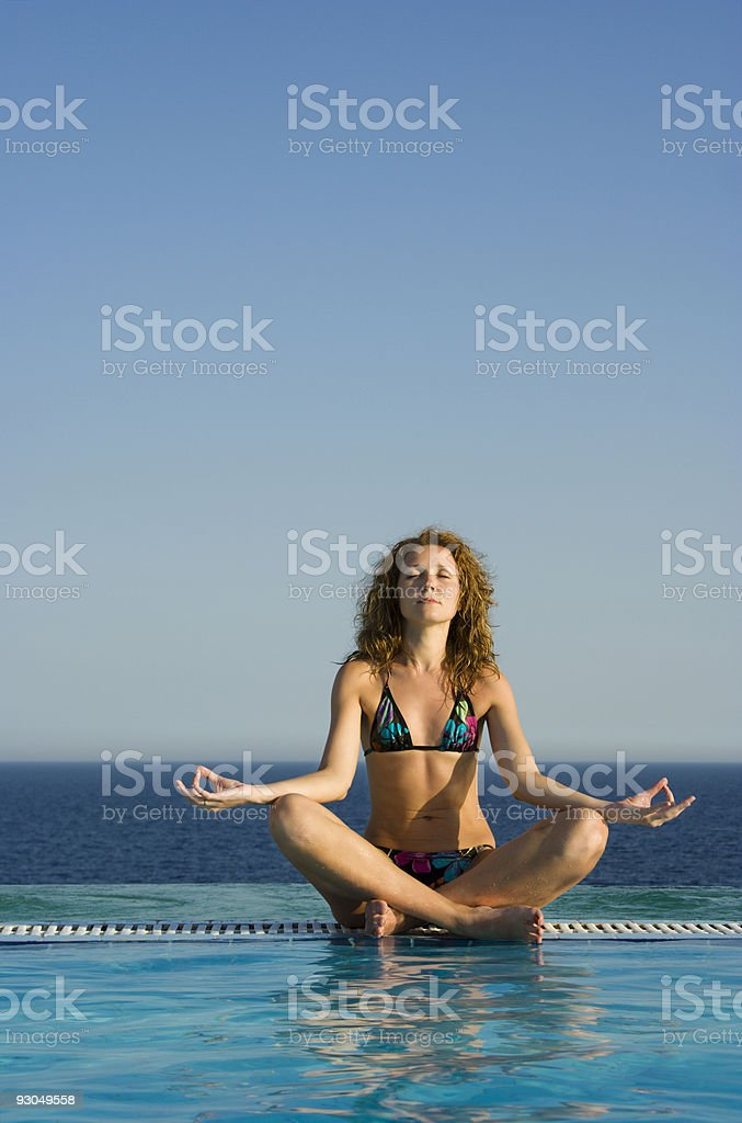 Beautiful girl meditating in the pool royalty-free stock photo