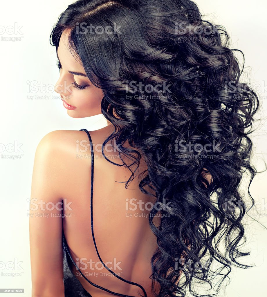 Beautiful girl model with long black curled hair. stock photo