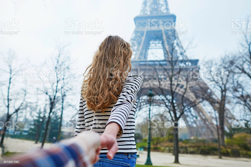 Beautiful girl near the Eiffel tower, follow me concept stock photo