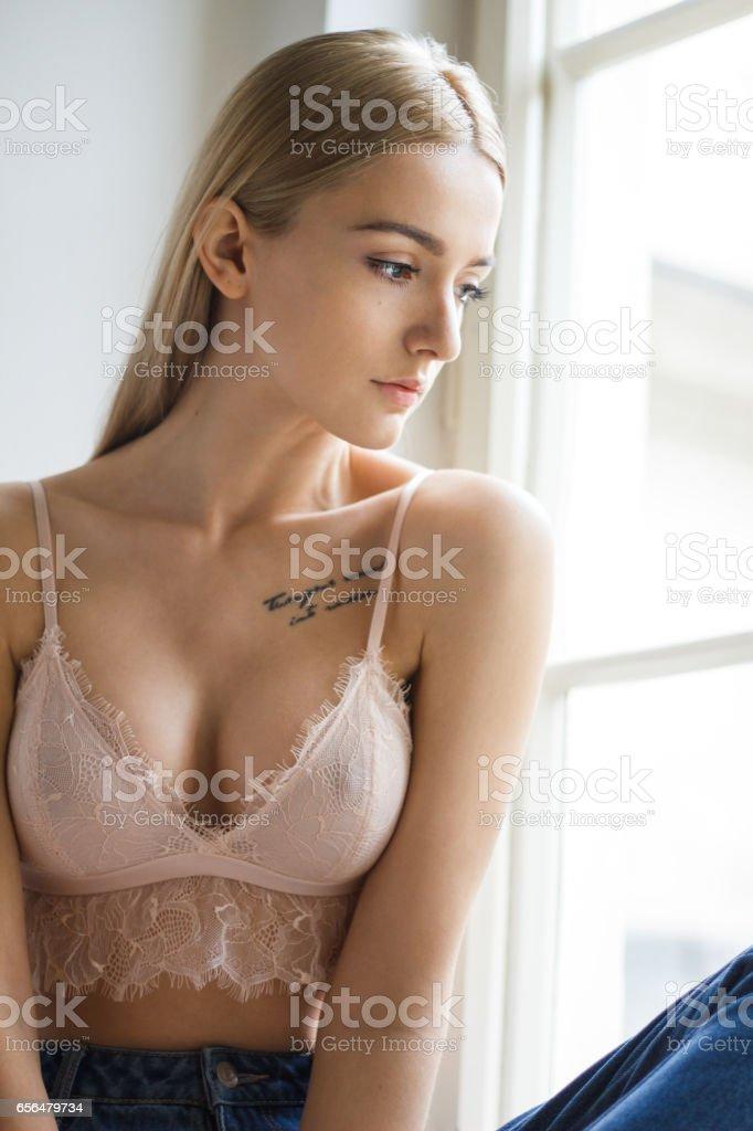 Beautiful girl next to window stock photo