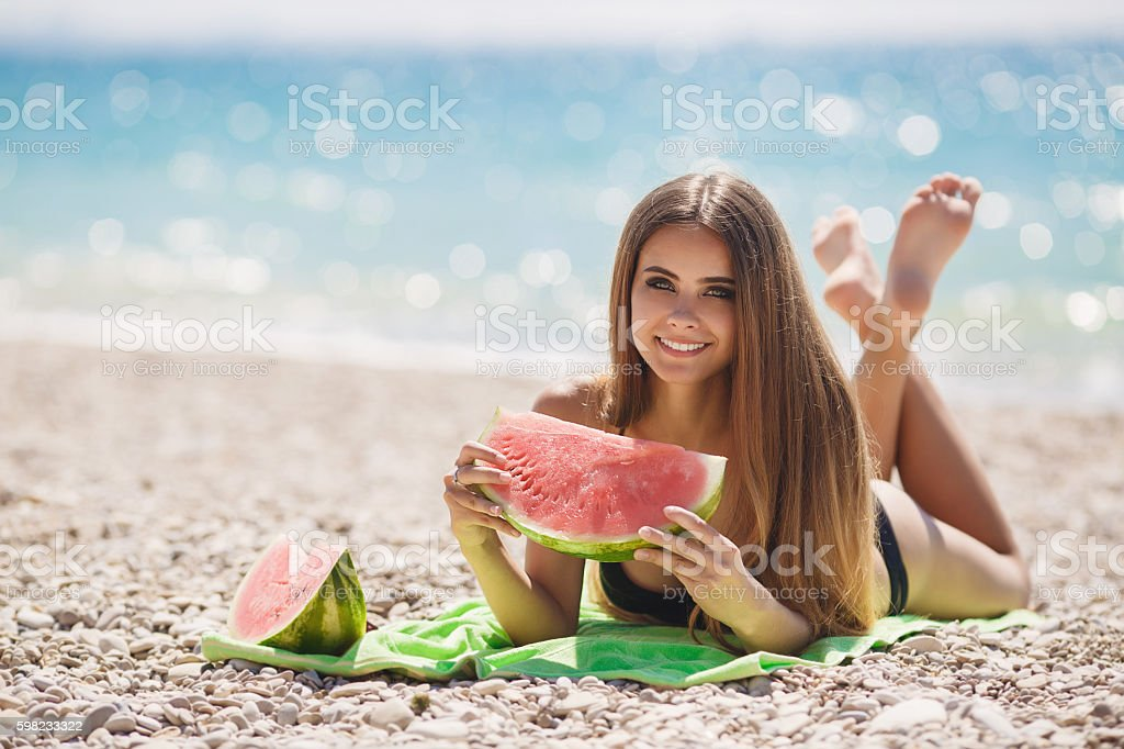 Beautiful girl on beach eating watermelon foto royalty-free