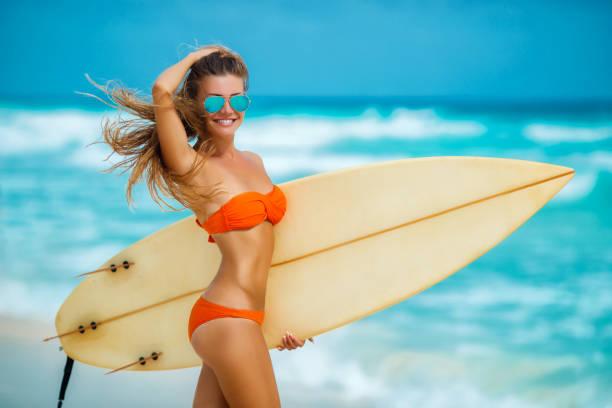 schöne mädchen am strand mit surfbrett - haare ohne lockenstab wellen stock-fotos und bilder