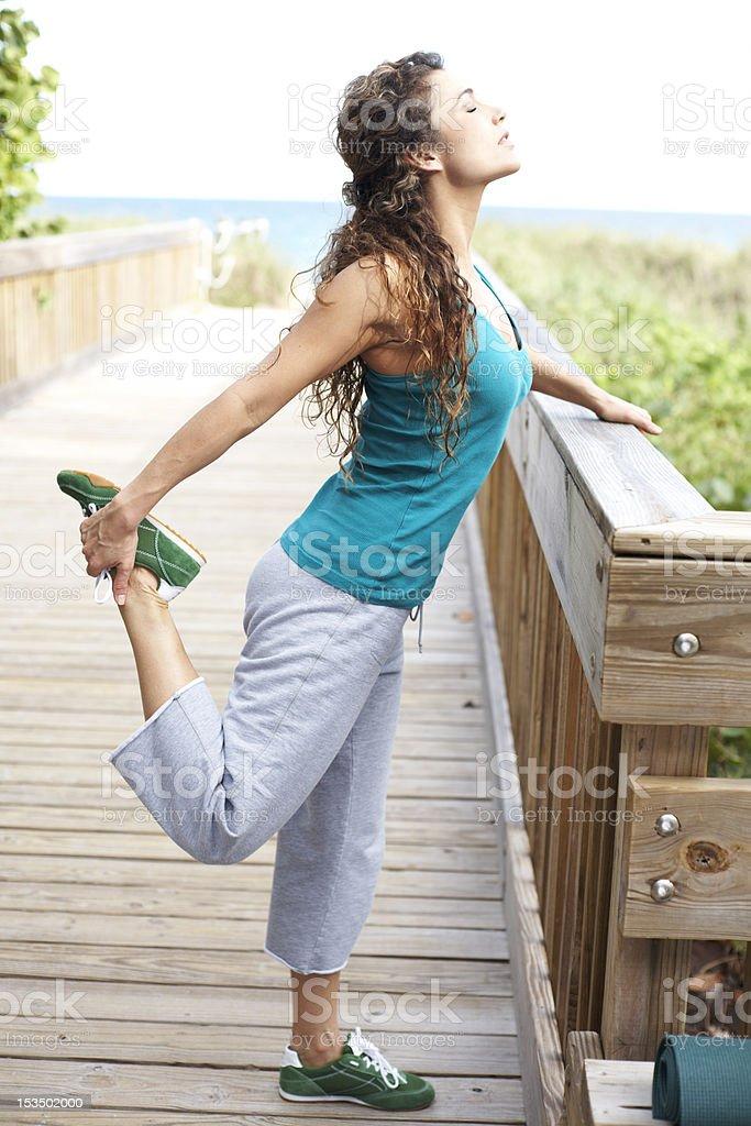 beautiful girl on boardwalk stretching royalty-free stock photo