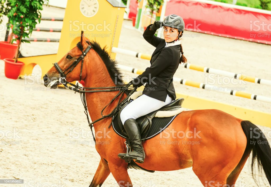 Light-brown horse and young woman in uniform going to jump.