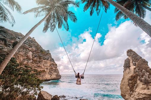 Beautiful girl on swing coconut palms on beach at Daimond  beach, Nusa Penida island Bali ,Indonesia