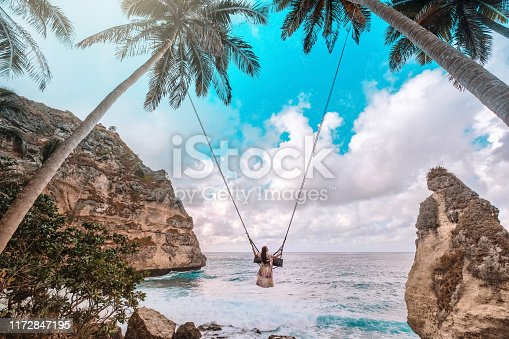 istock Beautiful girl on swing coconut palms on beach at Daimond  beach, Nusa Penida island Bali ,Indonesia 1172847195