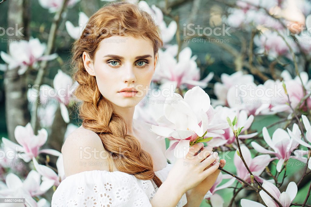 Beautiful girl on the background of spring bush