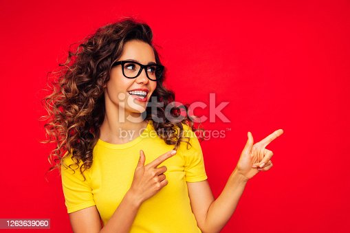 Beautiful girl on the red background showing right direction with her fingers
