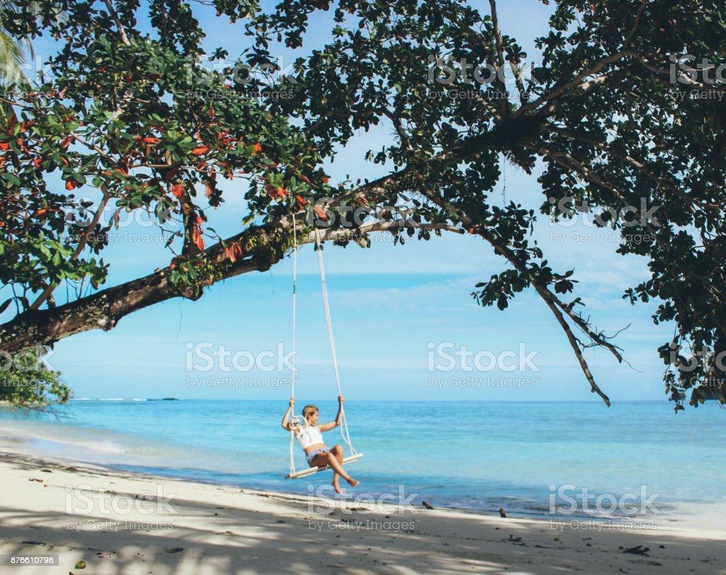 Beautiful girl on the swing on the beach stock photo