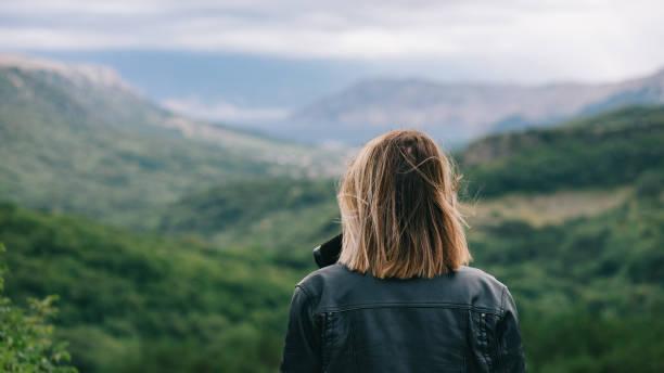Beautiful girl on top of mountain watching scenery stock photo