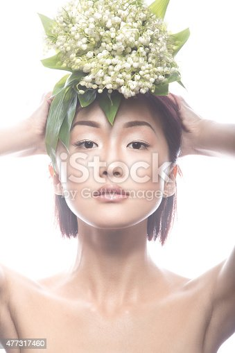 istock beautiful girl oriental type with delicate natural make-up and flowers. 477317460