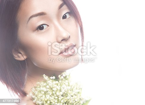 istock beautiful girl oriental type with delicate natural make-up and flowers. 477317466