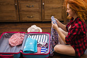 Beautiful young girl with long red curly hair packing suitcase for a holiday. Travel concept